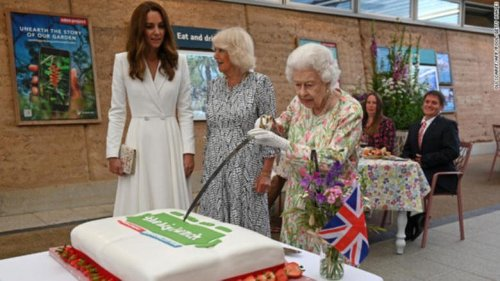 Queen Elizabeth insists on slicing a cake with a ceremonial sword as Kate Middleton watches during event in Cornwall, England