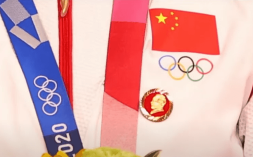 Chinese Olympians wear pins of Communist leader Mao on the medal podium