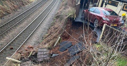 Train chaos as car teeters on bank edge after landslip blocks lines