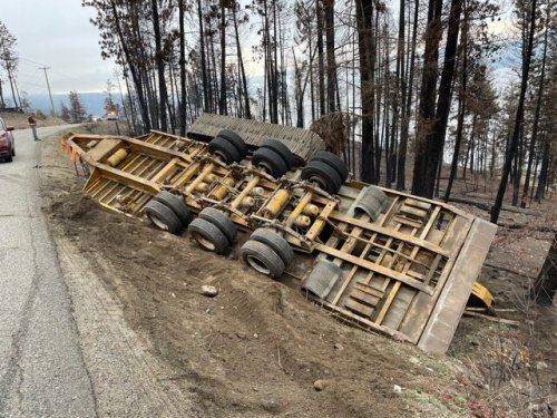Flatbed trailer hauling heavy earth-moving equipment overturned on Westside Road (Vernon)