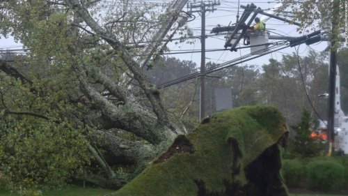 Crews are working to restore power to hundreds of thousands in New England as more flooding looms along East Coast