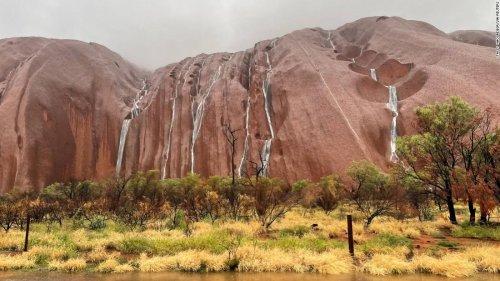 Water cascades down Uluru after heavy rains batter northern Australia