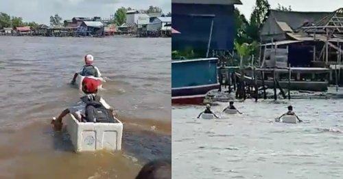 Elementary school boys cross river on styrofoam boxes in Indonesia (Video)