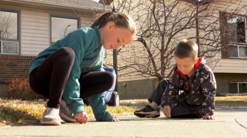 'I'm trying hard to keep it colourful': Cochrane kids take to the sidewalk in community art event.