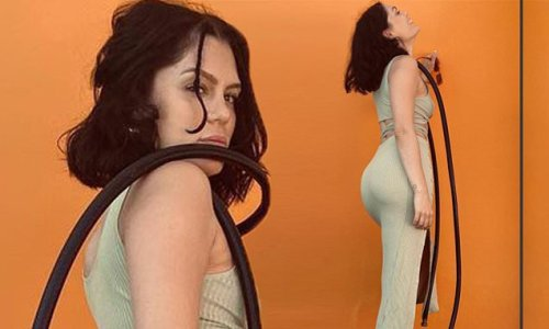 Jessie J shows off her slender physique as she poses with a hose