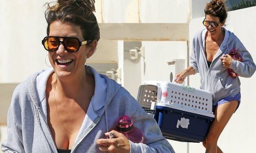 Kate Walsh puts on a leggy display as she carries her pet cat to car