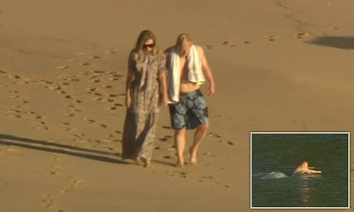 Trimmer-looking Boris walks hand-in-hand with Carrie on Cornish beach