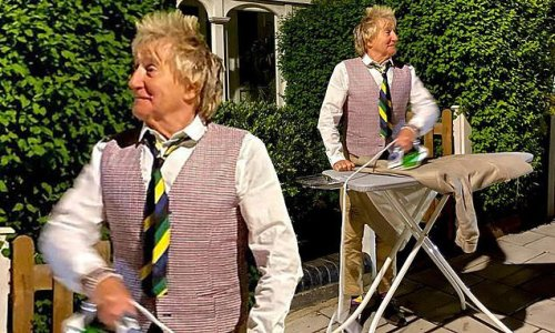 Rod Stewart stands out on the street ironing a brown shirt
