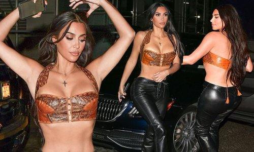 Kim Kardashian flashes her tiny tummy in a half-corset top