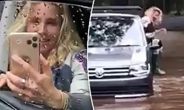 Elsa Pataky escapes through a car window in flooded Byron Bay street