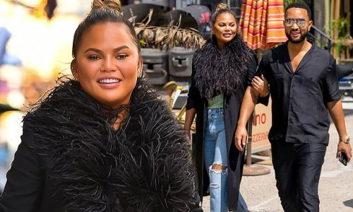 Chrissy Teigen is all smiles in feathered jacket with ripped jeans