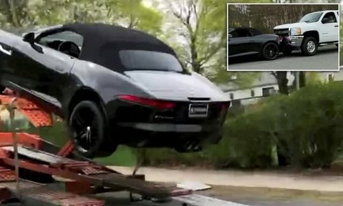 Jaguar is totalled when it slides off delivery lorry and into a truck