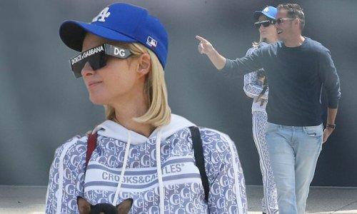 Paris Hilton cradles her Chihuahua in Malibu with fiancé Carter Reum