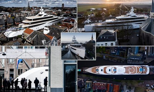 Pictured: New superyacht is carefully manoeuvred along narrow canals