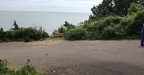 Woman falls 50ft onto beach after car plunges over cliffs