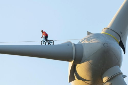 Man With Balls Of Steel Cycles Across The Blade Of A Wind Turbine To Make A Point About Renewable Energy
