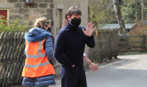 Tom Cruise waves to fans as he films Mission Impossible in English countryside