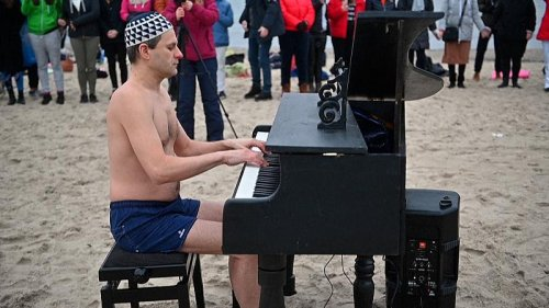 Swimsuit-clad Poles fundraise with chilly swim and beach piano tunes