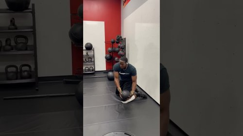Trainer does abs workout using gym ball