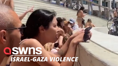 Beach goers in Tel Aviv take cover as rockets are fired from Gaza (RAW)