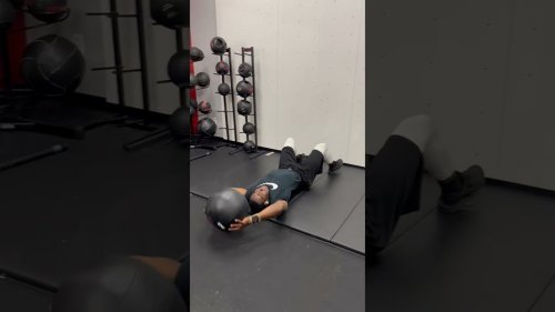 Bodybuilder does modified sit-ups with slam ball