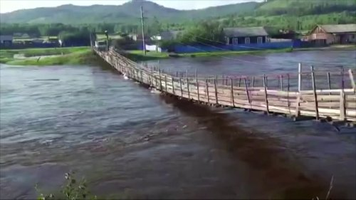 Suspension bridge collapses in flooded Russian river