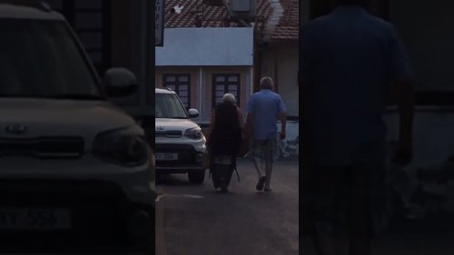 Elderly Couple Hold Hands While Walking