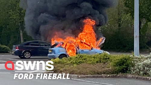 A man's car was seen engulfed in flames after it caught fire in a Tesco car park (RAW)