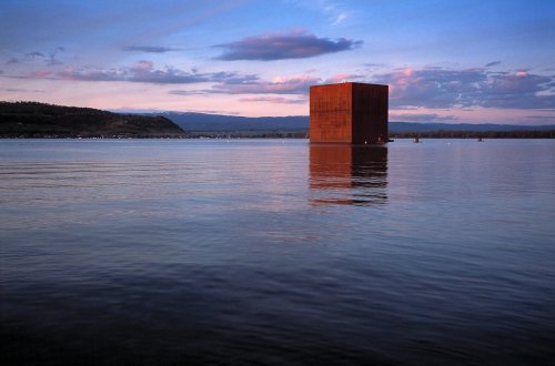 """For the 2002 Swiss national exhibition, the medieval town Murten (or Morat in French) had the motto """"Moment and Eternity"""". French architect Jean Nouvel designed this 34-meter rusty steel cube that appeared to float on the lake just off the shore. The interior consisted of three accessible levels with multiple spaces and hosted art installations such as video projections. Roughly every 25 years Switzerland hosts a national exhibition with the next planned for 2027."""
