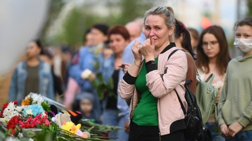 People lay flowers and soldiers stand guard outside Kazan school