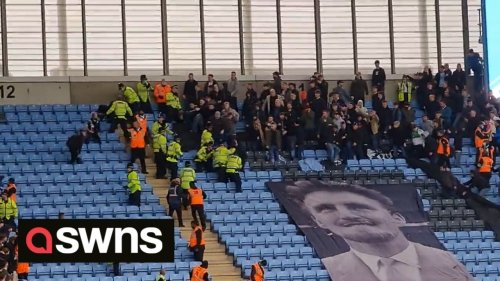 Violence erupts in the stands at a football match - above large banner of Jimmy Hill