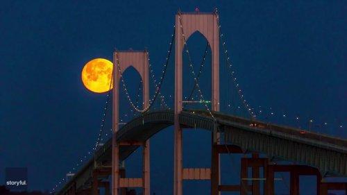 Snow Moon Changes From Orange to Pink as It Sets Behind Rhode Island's Newport Bridge