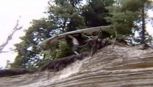 Man Tries to Surf Down a Large Hill of Dirt