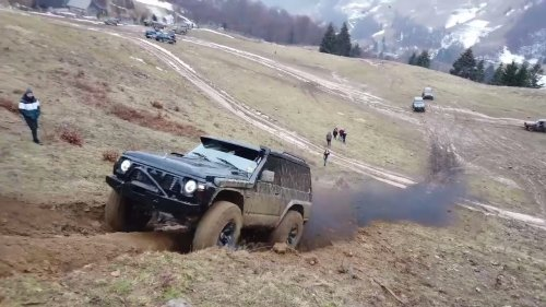 Diesel truck throws back smoke up an offroad hill