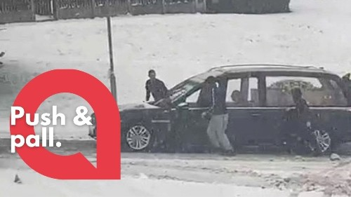 Strangers rushed out in freezing conditions to help a hearse up a hill after it got stuck in the snow