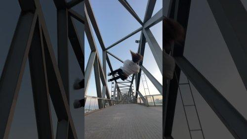 Athlete performs corkscrew flips on bridge