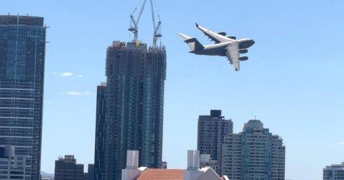 Riesiges Militärflugzeug im Tiefflug durch Häuserschluchten