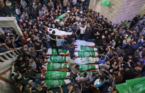 Palestinesi si riuniscono intorno ai corpi di 13 militanti di Hamas