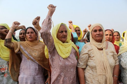 Women farmers shout slogans as they participate in the ongoing...