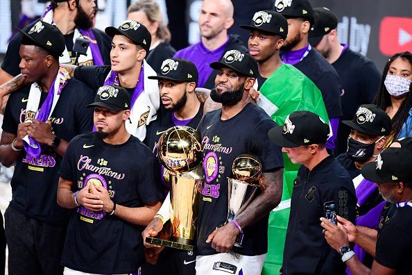LeBron James of the Los Angeles Lakers reacts with his MVP trophy and...