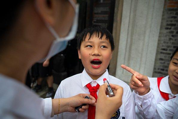 Una studentessa si prepara fuori dal Memoriale del Primo Congresso Nazionale del Partito Comunista Cinese