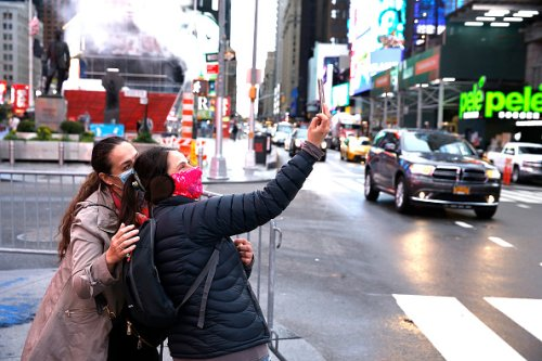 People wearing protective masks take a selfie in Times Square on...