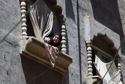 Una donna palestinese guarda il corteo funebre del capo militare di Hamas, Bassem Issa