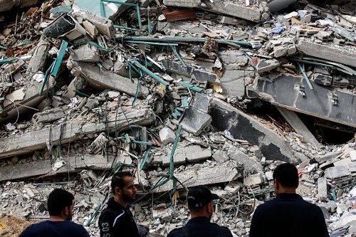 Palestinesi davanti a una torre distrutta dopo il cessate il fuoco a Gaza