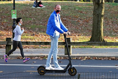 A man wearing a protective mask rides a scooter in Central Park on...