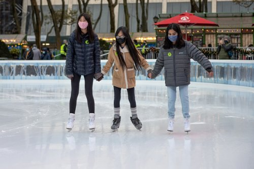 Women wearing masks hold hands while ice skating at the Bank of...