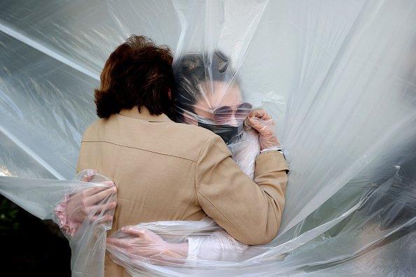 A hug through a plastic sheet