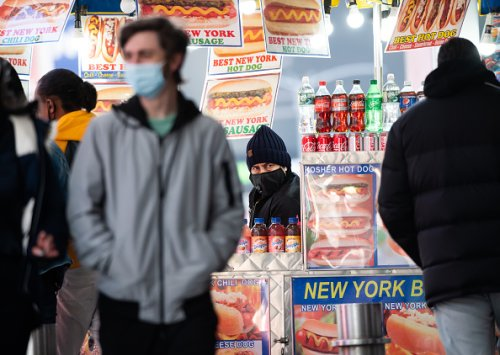 A hot dog stand worker wears a face mask in Times Square as the city...