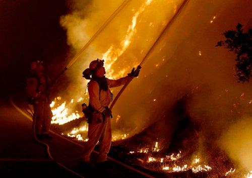 Sacramento firefighters light a backfire to prevent the Glass Fire...