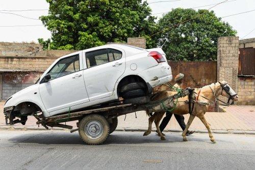 Un uomo trasporta un'auto su un carretto ad Amritsar in India